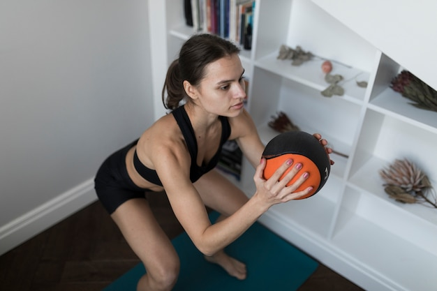 Hoge hoek van vrouw die oefeningen met bal doet