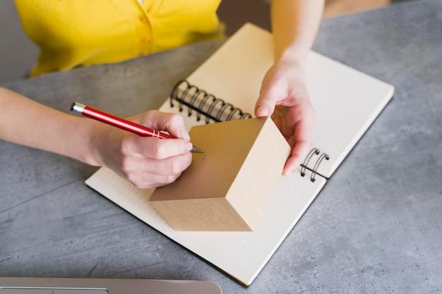 Hoge hoek van vrouw die op doos schrijft