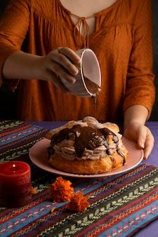 Hoge hoek van vrouw die pan de muerto decoreert met chocoladesiroop