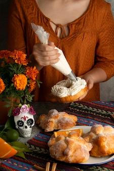 Hoge hoek van vrouw die pan de muerto decoreert met room