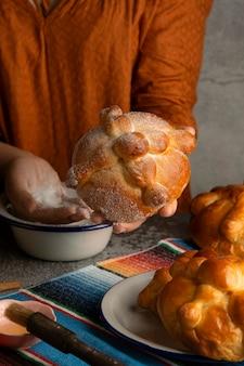 Hoge hoek van vrouw die pan de muerto decoreert met suiker