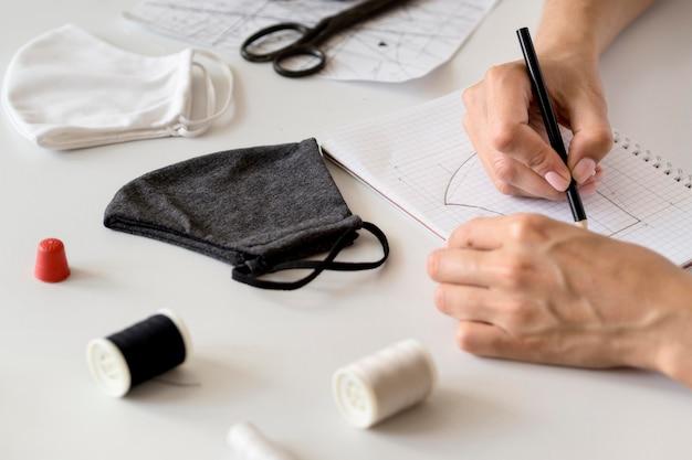 Hoge hoek van vrouw die te naaien gezichtsmasker ontwerpt