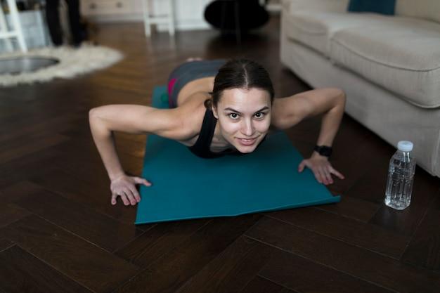 Hoge hoek van vrouw die yoga op mat met waterfles doet