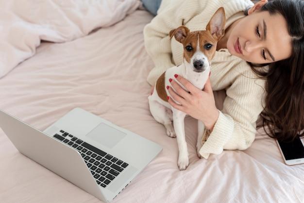 Hoge hoek van vrouw en hond in bed