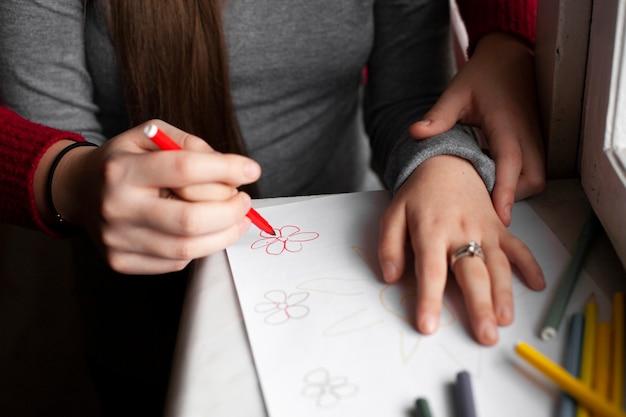 Hoge hoek van vrouw en meisje met down syndroom tekening