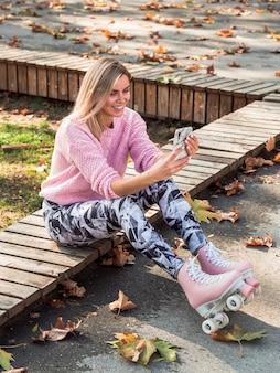 Hoge hoek van vrouw in beenkappen en rolschaatsen die selfie nemen
