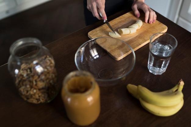 Hoge hoek van vrouw in de keuken die gezonde maaltijd voorbereidt