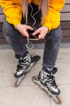 Hoge hoek van vrouw in rolbladen kijken naar smartphone