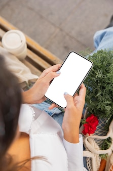 Hoge hoek van vrouw met behulp van haar smartphone buitenshuis