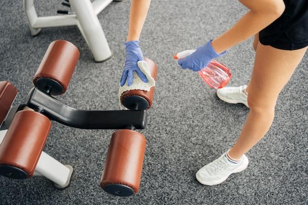 Hoge hoek van vrouw met handschoenen op de sportschool desinfecterende apparatuur