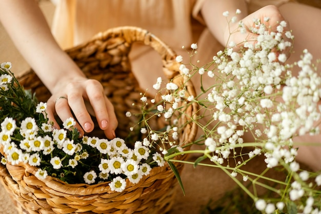 Hoge hoek van vrouw met mandje met lentebloemen
