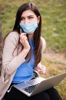 Hoge hoek van vrouw met medisch masker dat in openlucht met laptop werkt