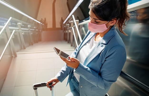 Hoge hoek van vrouw met medisch masker en bagage met behulp van smartphone op de luchthaven tijdens pandemie