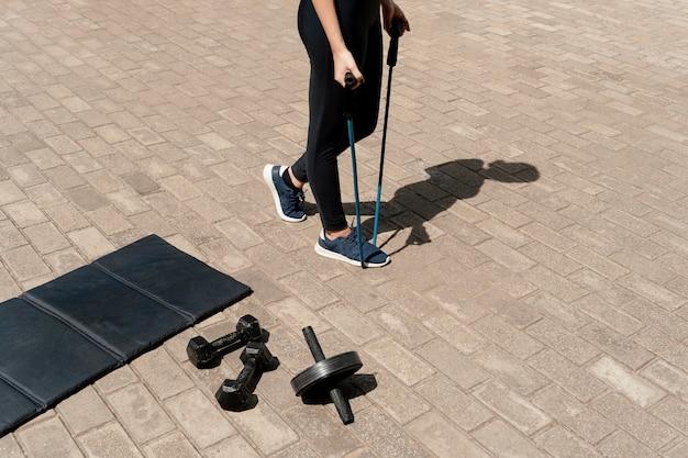 Hoge hoek van vrouw met trainingsapparatuur buitenshuis