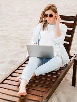 Hoge hoek van vrouw op strandstoel die aan laptop werkt