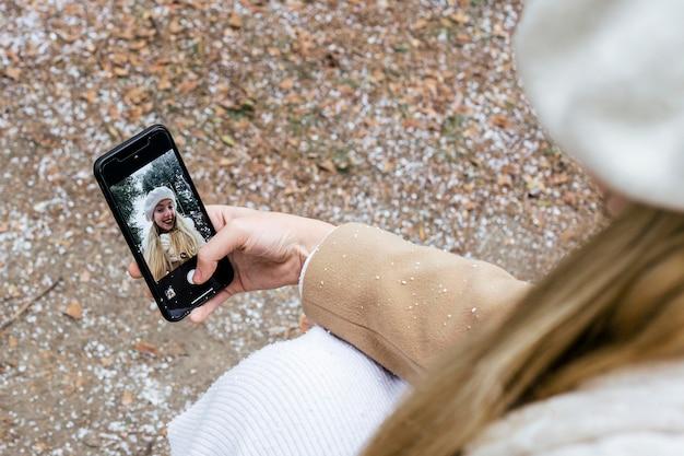 Hoge hoek van vrouw selfie te nemen in het park tijdens de winter
