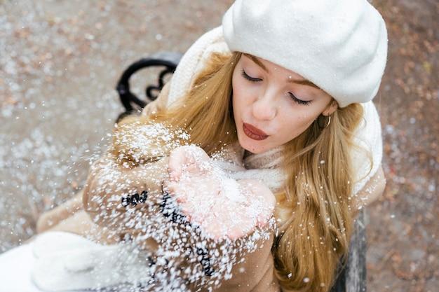 Hoge hoek van vrouw waait sneeuw in het park in de winter