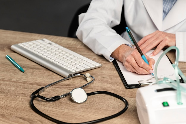 Hoge hoek van vrouwelijke arts die een recept schrijft bij bureau
