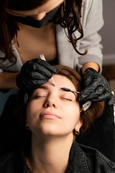 Hoge hoek van vrouwelijke arts die een wenkbrauwbehandeling voor vrouw doet