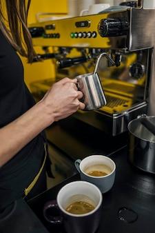 Hoge hoek van vrouwelijke barista opschuimende melk