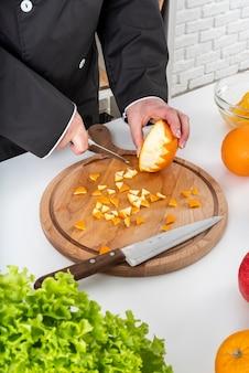 Hoge hoek van vrouwelijke chef-kok die een sinaasappel snijdt