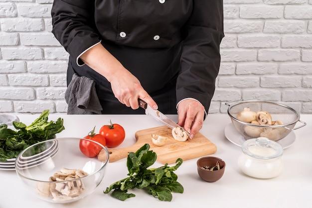 Hoge hoek van vrouwelijke chef-kok snijden champignons en tomaten