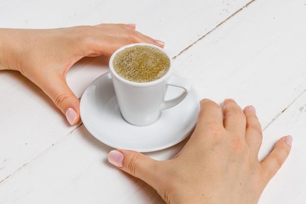 Hoge hoek van vrouwelijke handen houden een kopje sterke koffie