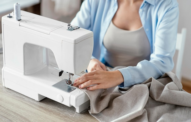 Hoge hoek van vrouwelijke kleermaker met behulp van naaimachine in de studio