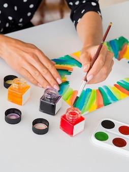 Hoge hoek van vrouwelijke kunstenaar schilderen met aquarel