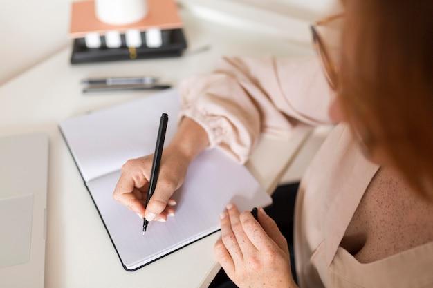 Hoge hoek van vrouwelijke leraar aan balie tijdens online les