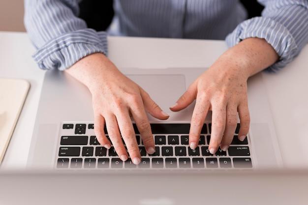 Hoge hoek van vrouwelijke leraar met behulp van de laptop om te schrijven tijdens online les