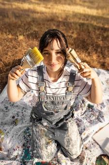 Hoge hoek van vrouwelijke schilder met verfborstels