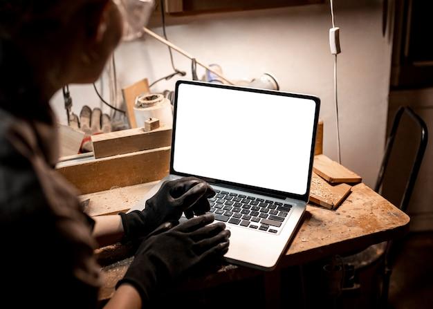 Hoge hoek van vrouwelijke timmerman met behulp van laptop