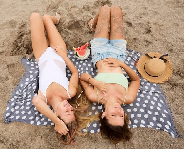 Hoge hoek van vrouwelijke vrienden ontspannen op het strand