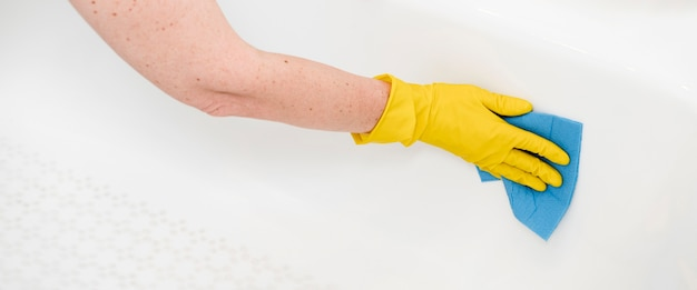 Hoge hoek van vrouwen schoonmakende badkuip