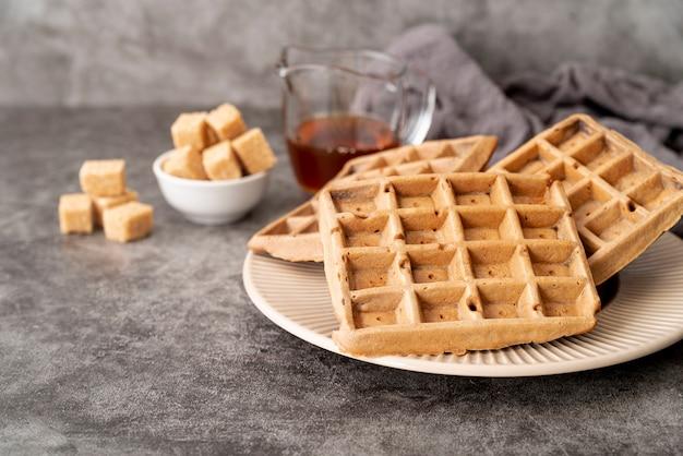 Hoge hoek van wafels op plaat met suikerklontjes en stroop