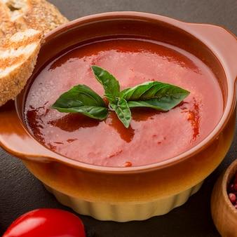 Hoge hoek van winter tomatensoep in kom met brood