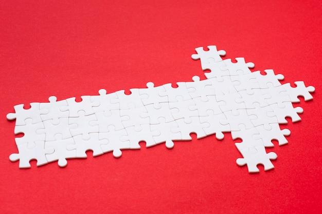 Hoge hoek van witte pijl uit puzzelstukjes