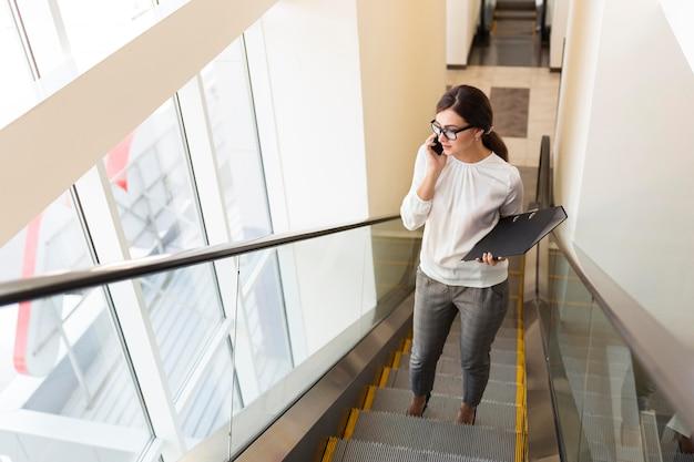 Hoge hoek van zakenvrouw met bindmiddel praten over de telefoon terwijl op roltrap