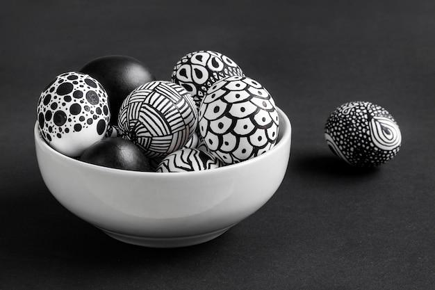 Hoge hoek van zwart-wit eieren voor pasen in kom