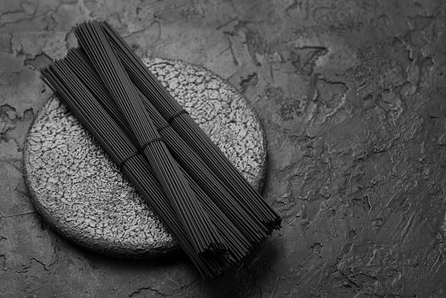 Hoge hoek van zwarte spaghetti bundels op leisteen