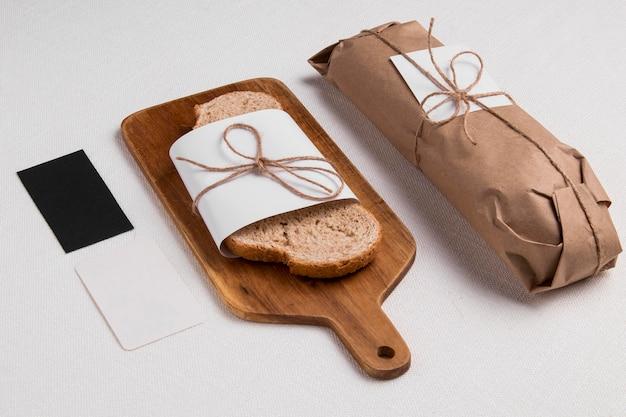Hoge hoek verpakte sneetje brood op snijplank met stokbrood