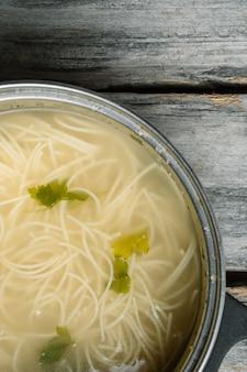 Hoge hoek verticaal een zelfgemaakte soep met spaghetti en groenen op een houten oppervlak