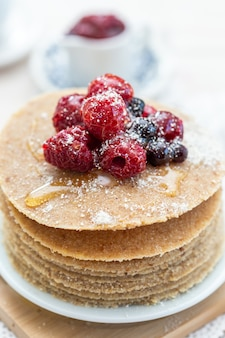 Hoge hoek verticale close-up shot van rauwe veganistische pannenkoeken met honing en bessen