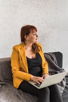 Hoge hoek vrouw die op laptop werkt