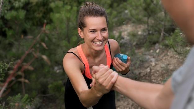 Hoge hoek vrouw klimmen door te worden geholpen door een vriend