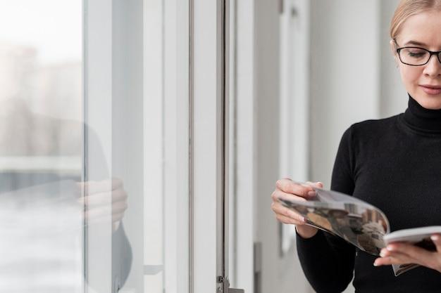 Hoge hoek vrouw leest tijdschrift