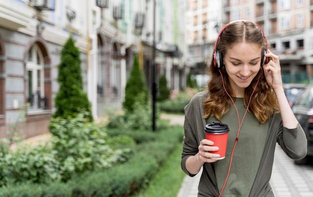 Hoge hoek vrouw met koffie en koptelefoon