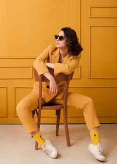 Hoge hoek vrouw met zonnebril op stoel