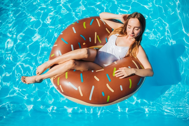 Hoge hoek vrouw poseren en glimlachend in donut zwemmen ring
